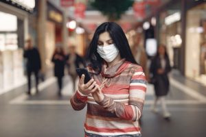 Indian woman looks at phone in shopping mall while wearing face mask