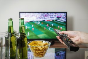 Person's hand holding TV remote with chips, beer and a soccer game on the TV in the background