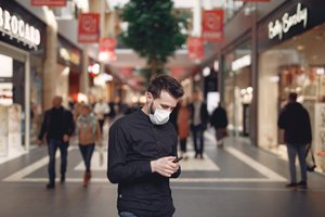 Man in disposable mask using smartphone