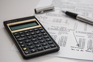 Calculator, pen and paper - budgeting