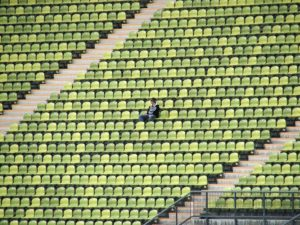 One person sits in a stadium with empty chairs.