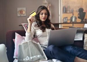 Une femme tient une carte de crédit lors de ses achats en ligne