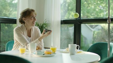 Actrice assise à une table et parlant à une balle de tennis