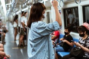 Femme debout dans un wagon de métro et portant un masque