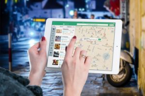 gros plan d'une tablette affichant une carte géographique et tenue par les mains d'une femme à l'extérieur, sur une rue en soirée
